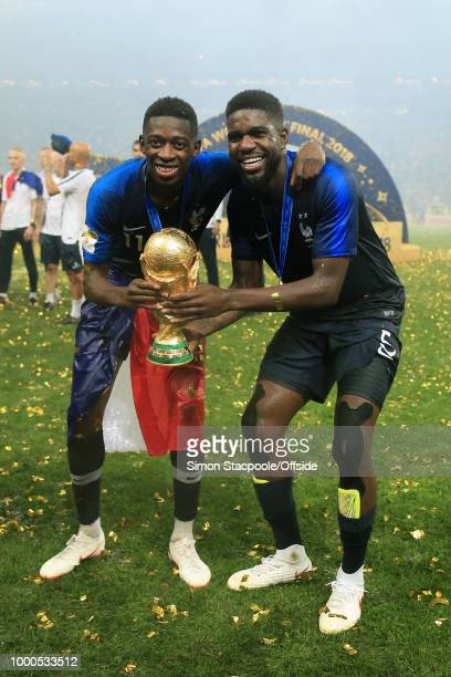 Ousmane Dembele of France and teammate Samuel Umtiti pose with the trophy after the 2018 FIFA World Cup Russia Final between France and Croatia at...