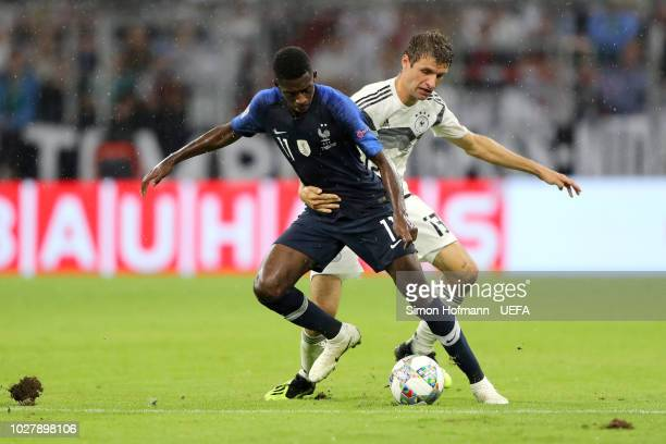 Ousmane Dembele of France is challenged by Thomas Mueller of Germany during the UEFA Nations League Group A match between Germany and France at...