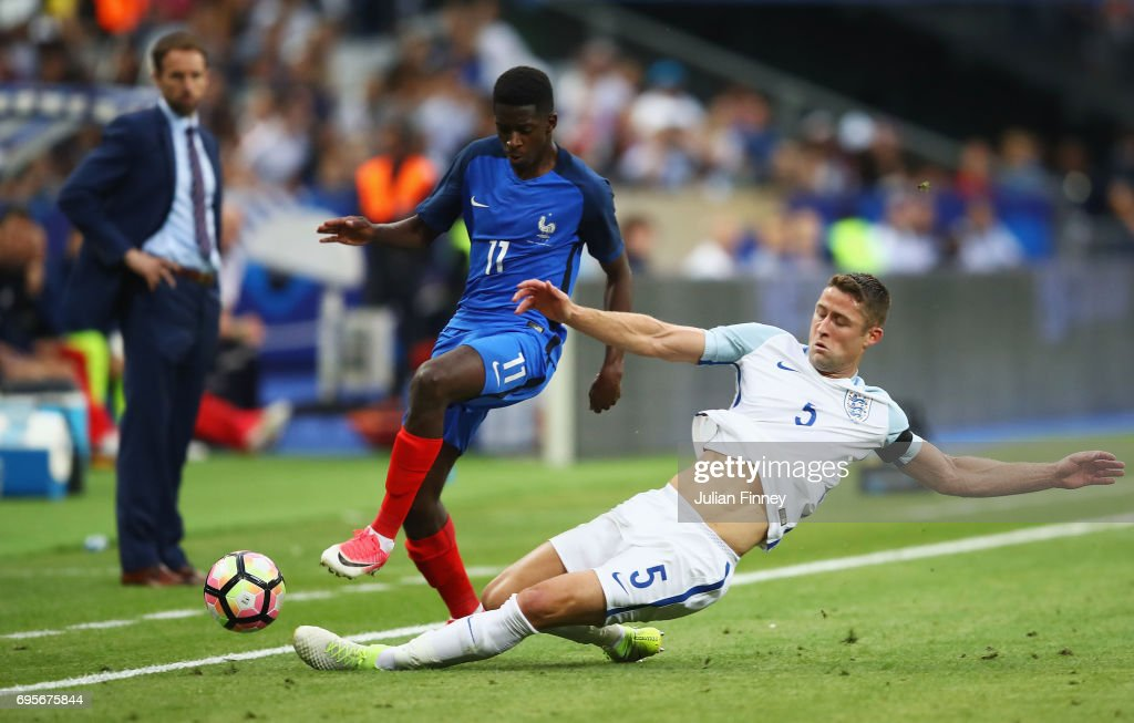 Ousmane Dembele of France is tackled by Gary Cahill of England during the International Friendly match between France and England at Stade de France on June 13, 2017 in Paris, France.