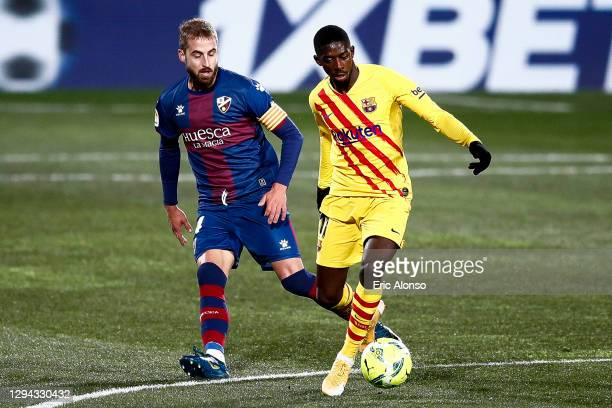 Ousmane Dembélé of FC Barcelona competes for the ball with Jorge Pulido of SD Huesca during the La Liga Santander match between SD Huesca and FC...