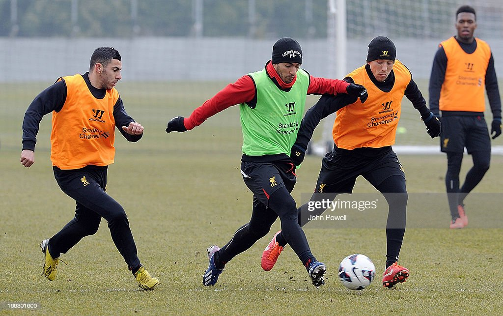 Oussama Assaidi, Luis Suarez and Lucas Leiva of Liverpool in action during a training session at Melwood Training Ground on April 11, 2013 in Liverpool, England.