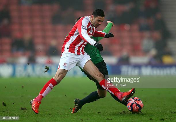 Oussama Assaidi of Stoke City battles for the ball with Rob Evans of Wrexham during the FA Cup Third Round match between Stoke City and Wrexham at...