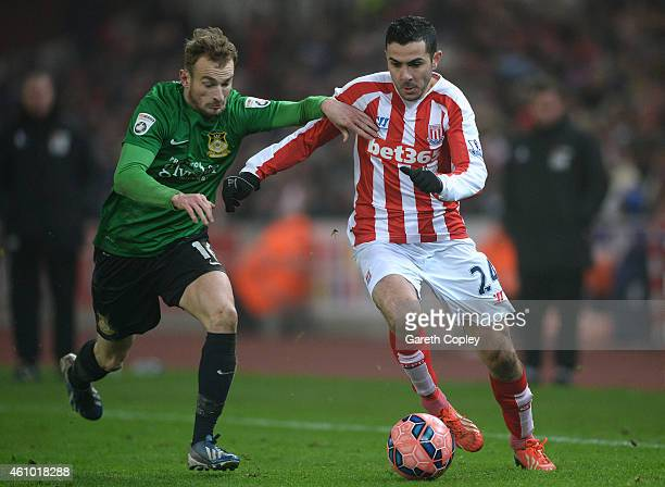Oussama Assaidi of Stoke City runs with the ball under pressure from Wes York of Wrexham during the FA Cup Third Round match between Stoke City and...