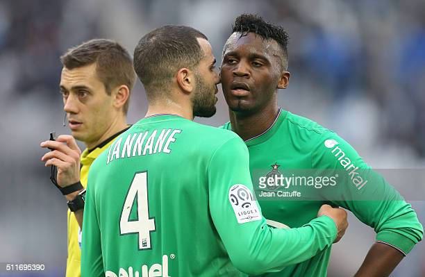 Oussama Tannane of SaintEtienne talks to teammate JeanChristophe Bahebeck while referee Clement Turpin looks on during the French Ligue 1 match...