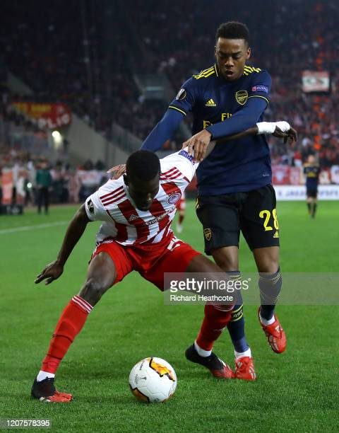 Ousseynou Ba of Olympiacos FC battles for possession with Joe Willock of Arsenal during the UEFA Europa League round of 32 first leg match between...