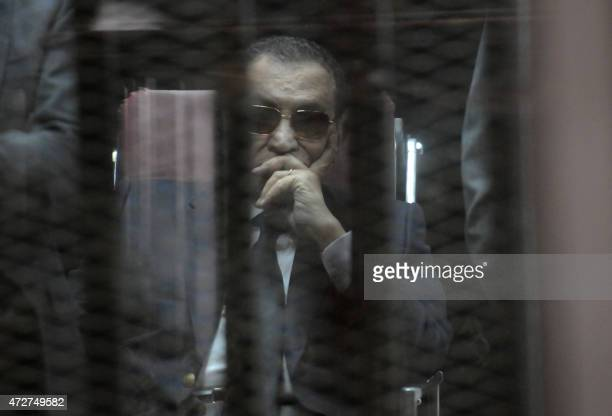 Ousted Egyptian president Hosni Mubarak sits in the defendants cage during his verdict hearing in a retrial for embezzlement on May 9, 2015 in the...