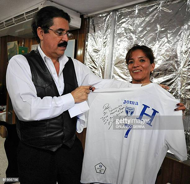 Ousted Honduran President Manuel Zelaya and his wife Xiomara Castro de Zelaya display a jersey sent to him as a gift by the captain of the national...