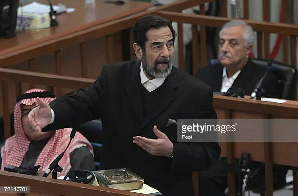 Ousted Iraqi leader Saddam Hussein gestures as Sultan Hashim Ahmad alJaburi alTai and Sabir Aba alAziz look on during their trial in the heavily...