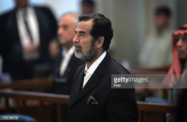 Ousted Iraqi leader Saddam Hussein stands as a witness is sworn in for testimony during his trial in the heavily fortified Green Zone October 19 2006...