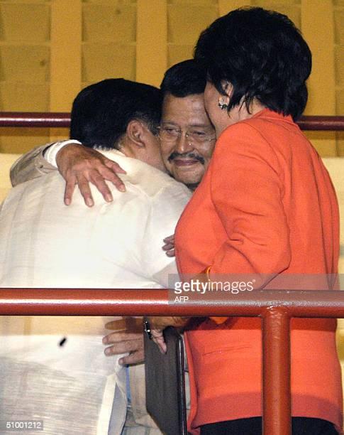 Ousted Philippine president Joseph Estrada embraces his eldest son newly elected senator Jose 'Jinggoy' Estarda with his wife senator luisa Ejercito...