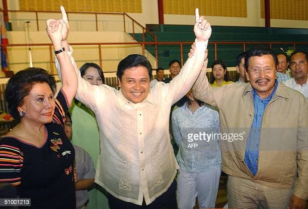 Ousted Philippine president Joseph Estrada with his wife senator luisa Ejercito raise the hand of their eldest son newly elected senator Jose...