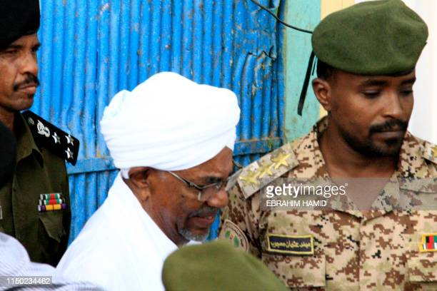 Ousted Sudanese leader Omar alBashir is escorted before being driven in an armed convoy from the Kober prison to the prosecutor's office in North...