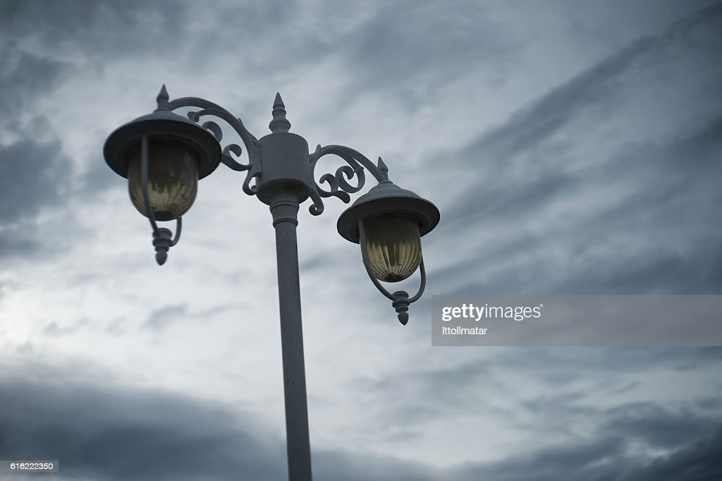 out door vintage ancient lamp with cloudy sky background : Stock Photo