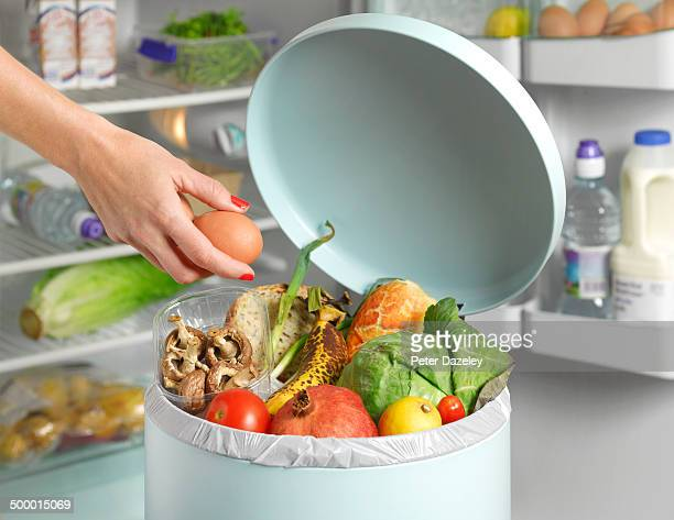 out of date in garbage bin in front of fridge - garbage bin stock pictures, royalty-free photos & images