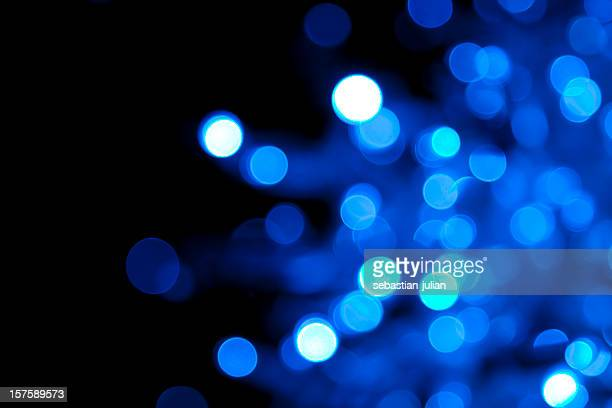 Out of focus illuminated blue dots on black background