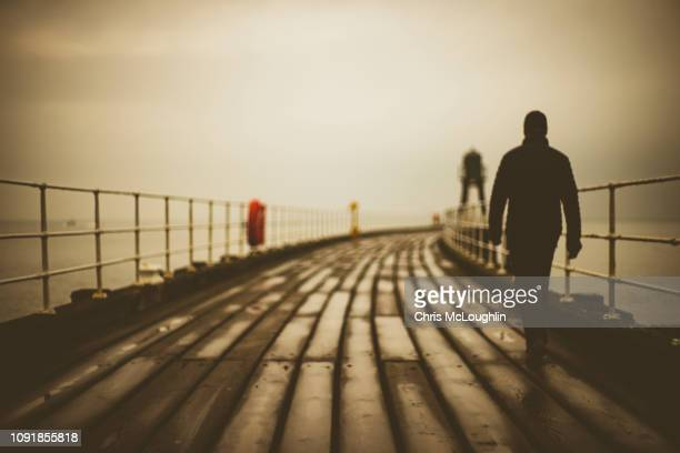 out of focus person walking on whitby pier, north yorkshire - northern rail stock pictures, royalty-free photos & images