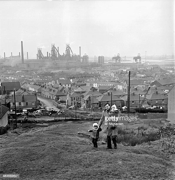Out of work steel worker Peter Dixon with his children walking through the industrial landscape of Port Talbot Wales 15th January 1964