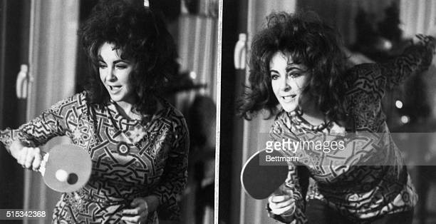 "Out to win, Elizabeth Taylor takes on husband, played by Michael Caine, in a game of table tennis. The scene is from Miss Taylor's new movie, ""Zee..."