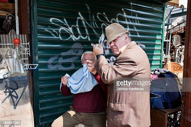 CONTENT] Outdoor barber cuts client's hair in Monastiraki flea market Athens Greece 2012