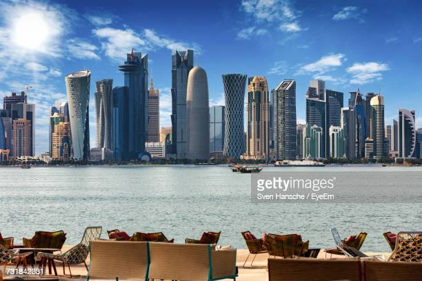 outdoor cafe by river against skyline in city - doha stock pictures, royalty-free photos & images