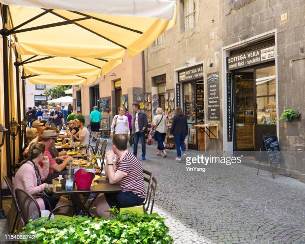 outdoor cafes and restaurants and retail souvenir shops in orvieto, italy - orvieto stock pictures, royalty-free photos & images