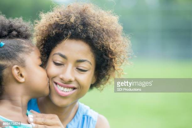 outdoor closeup portrait of little girl kissing mother's cheek - black mothers day stock pictures, royalty-free photos & images