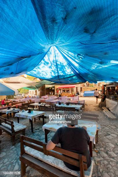 outdoor coffee shop with few customers under a blue sunshade at adatepe village. village - emreturanphoto stock pictures, royalty-free photos & images