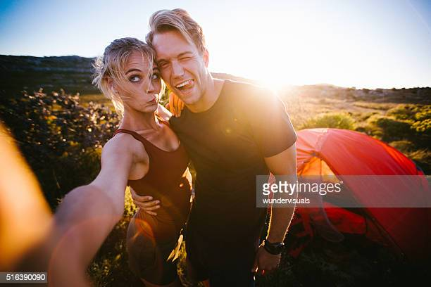 Outdoor couple taking sunset selfie while camping on hiking vaca