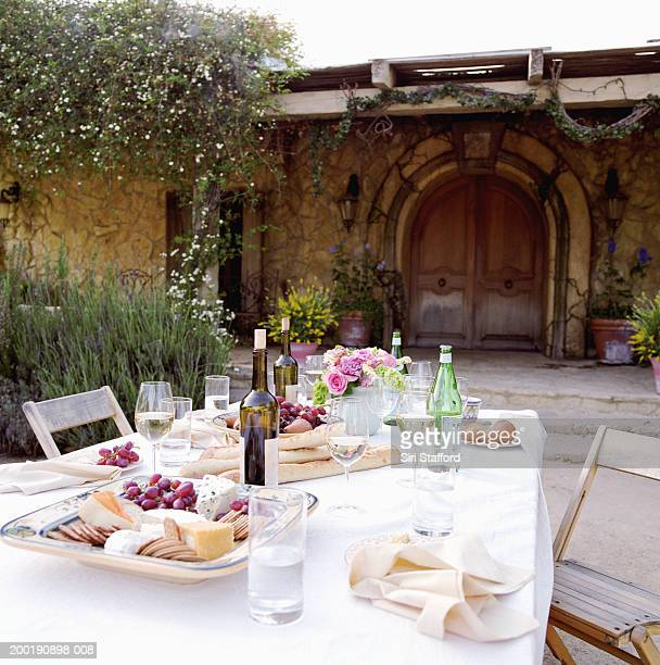 Outdoor dining table with wine bottles, fruits and cheeses
