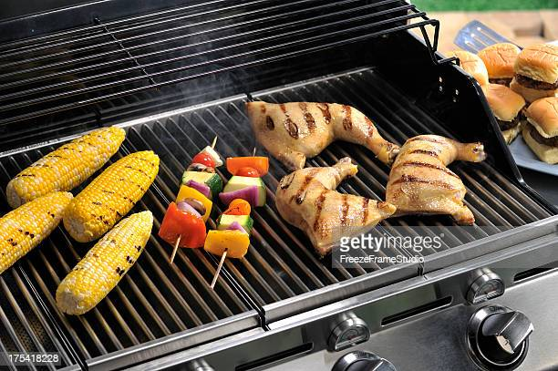 Outdoor Grilling on modern BBQ grill; corn, kabobs, chicken thighs