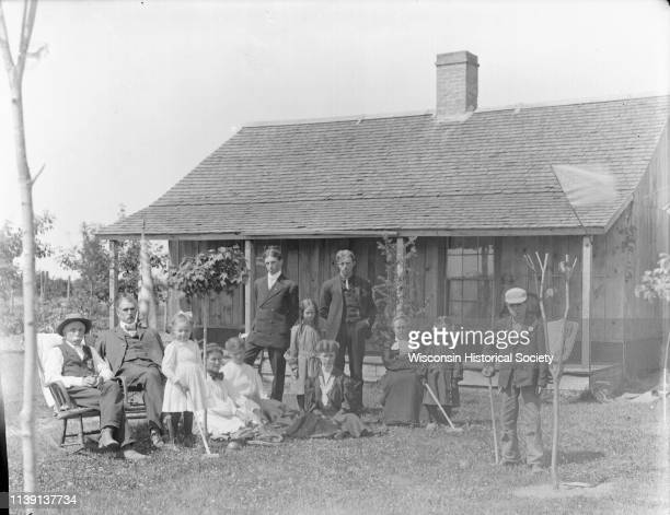 Outdoor group portrait in an identified location of a group of European American people posing in the yard of a small wooden cottage Black River...