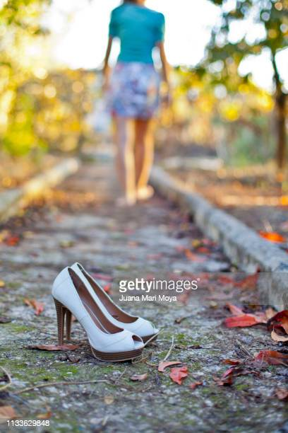 Outdoor heeled shoes in autumn and barefoot girl in the background.  Spain
