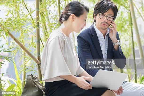 屋外ミーティング、日本の携帯電話で話している実業家、女性実業家、ノートパソコン
