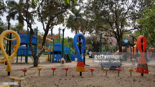 outdoor play equipment at playground against trees in park - ジャングルジム ストックフォトと画像