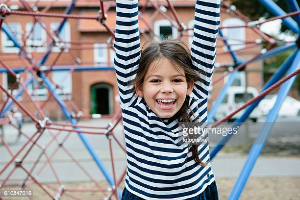 outdoor portrait: cute laughing at playground schoolgirl, looking at camera
