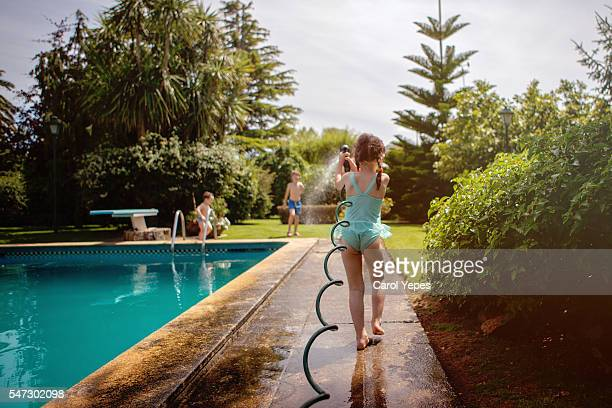 Outdoor portrait of 3 year old girl in swimming suit spraying garden hose. (summer water play)