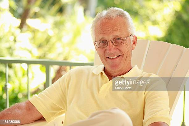 Outdoor portrait of a 60 year old man sitting on a