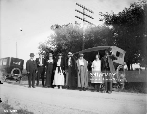 Outdoor portrait of a European American group including four women three men and a girl posing standing by two cars on the side of a road Black River...