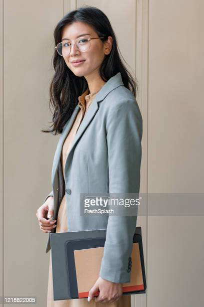 outdoor portrait of a happy asian businesswoman holding files, looking at camera - beige dress stock pictures, royalty-free photos & images