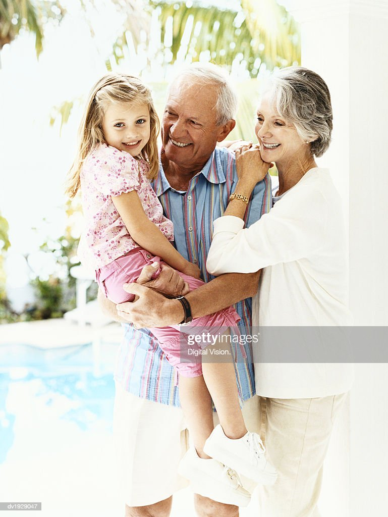 Outdoor Portrait of a Senior Couple and Their Young Granddaughter : Stock Photo