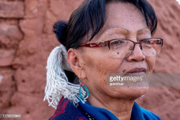 verticale extérieure d'une femme amérindienne aînée de navajo devant un hogan traditionnel dans la vallée de monument arizona - apache photos et images de collection