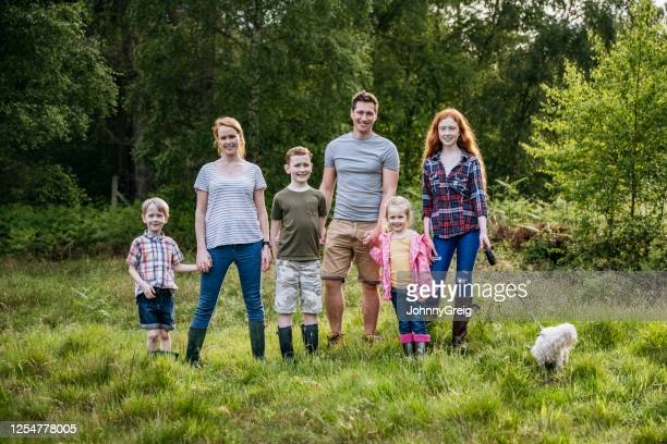 outdoor portrait of active family with four children and dog - organised group photo stock pictures, royalty-free photos & images