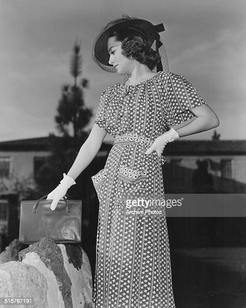 Outdoor portrait of actress Olivia de Havilland wearing a printed dress hat and gloves circa 1939