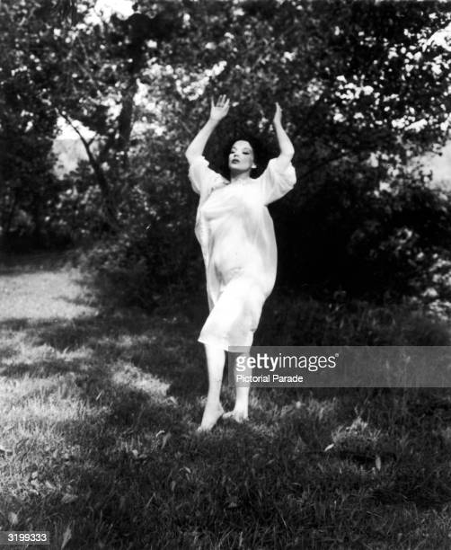 Outdoor portrait of American stripper dancer and burlesque performer Blaze Starr as she dances in the shade of a tree 1959