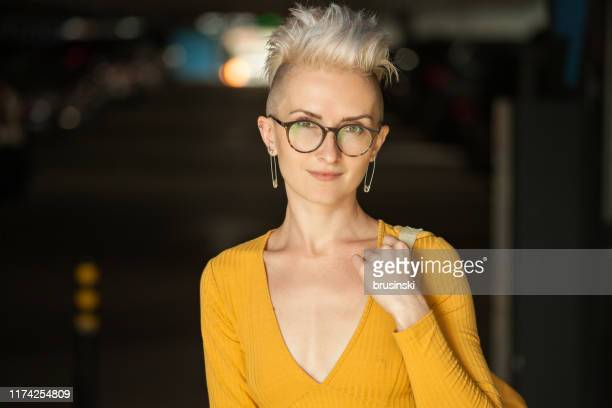 outdoor portrait of an attractive 30 year old woman in a yellow dress with a iroquois haircut - alternative lifestyle stock pictures, royalty-free photos & images