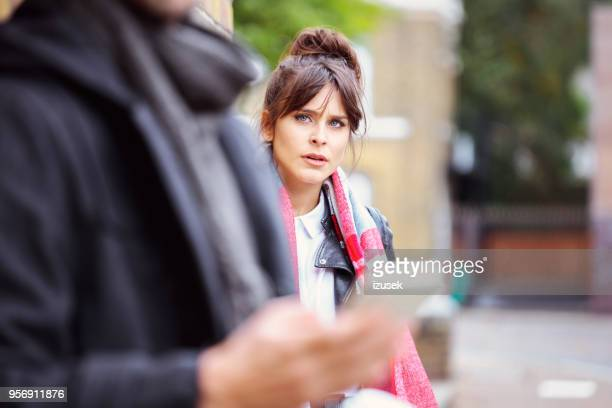Retrato al aire libre de la mujer enojada con su novio en el frente