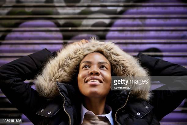 驚きに見上げる黒人女性の屋外肖像画 - 毛皮の飾り ストックフォトと画像