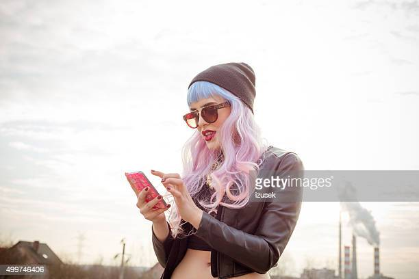 outdoor portrait of blue-pink hair cool girl texting on phone - tienermeisjes stockfoto's en -beelden