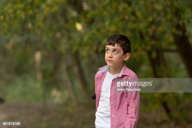 Outdoor portrait of boy looking up