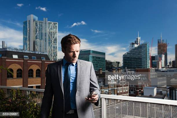 Outdoor portrait of businessman using smart phone
